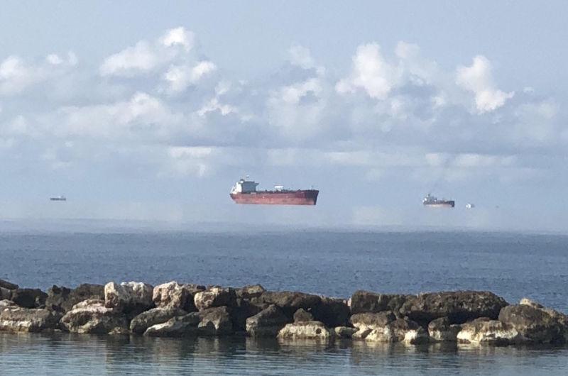 Esta foto com vários barcos flutuando no ar não é produto de Photoshop
