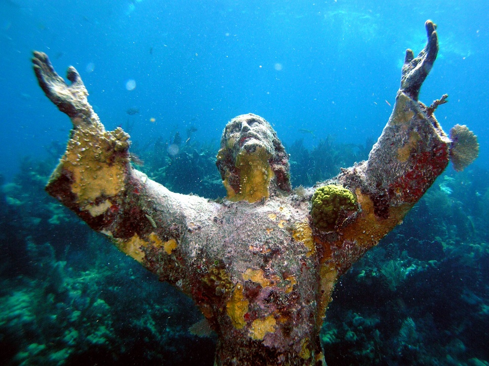 Estátua de Cristo coberta de corais no fundo do oceano Atlântico, perto da costa de Key Largo no Estados Unidos. Por Shutterstock.