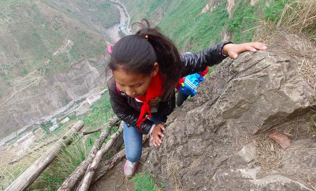 Crianças escalaminham um despenhadeiro de mil metros para ir à escola