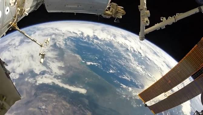 Um astronauta da NASA filma sua caminhada espacial tendo a Terra como papel de parede
