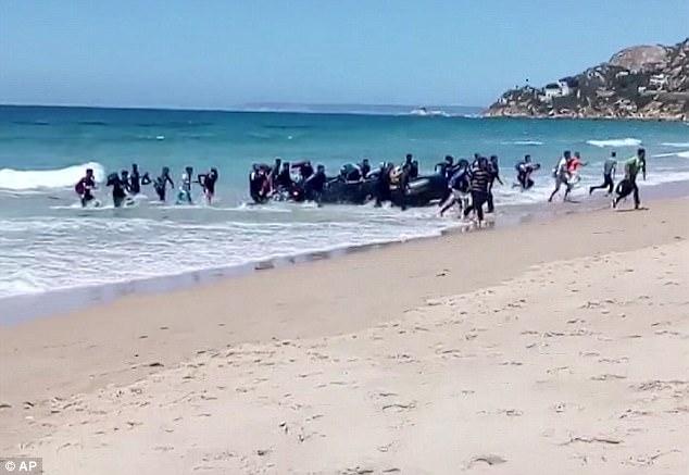 Banhistas ficam impressionados com a chegada de migrantes em uma praia espanhola