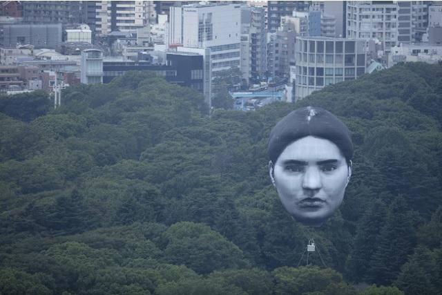 Uma cabeça gigante flutuante aparece no céu acima do centro de Tóquio